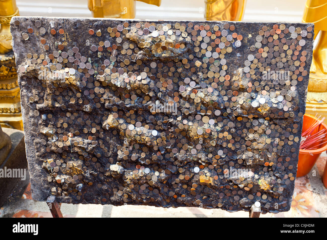 Donated Coins glued to a Board in the Temple Wat Phra That Doi Suthep near Chiang Mai in Thailand - Stock Image