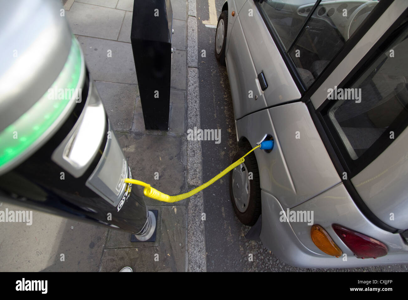 g-whiz Electric car at charging point in London; with charge point operated by Source London UK - Stock Image
