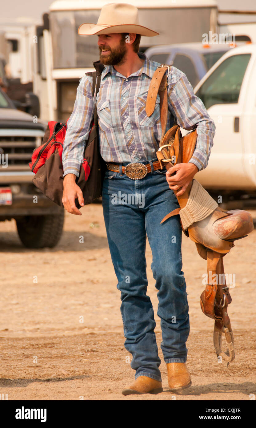 Cowboy bronc rider carrying his saddle to the Rodeo Arena, Bruneau, Idaho,USA - Stock Image