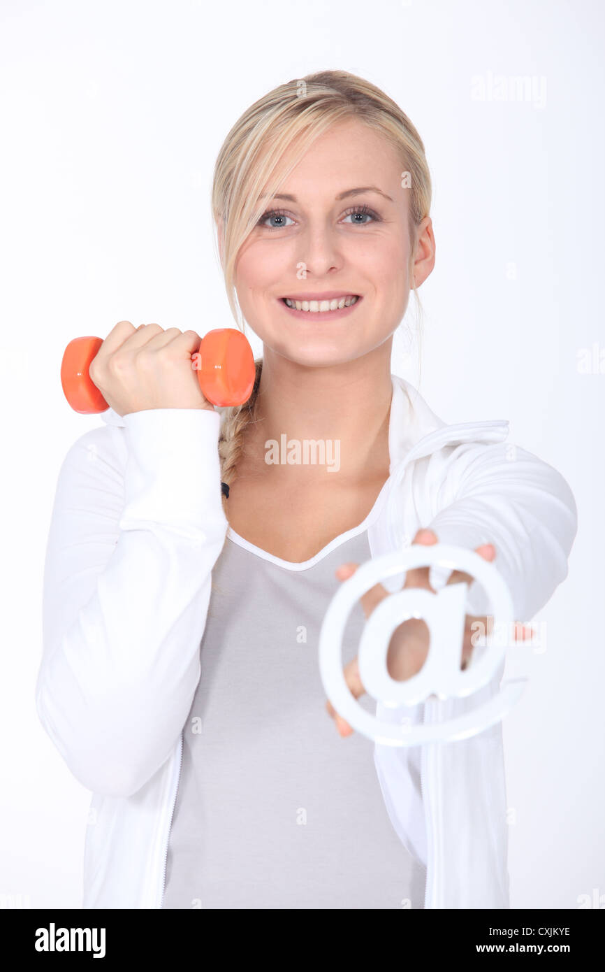 Young woman with a dumbbell and an internet @ sign - Stock Image