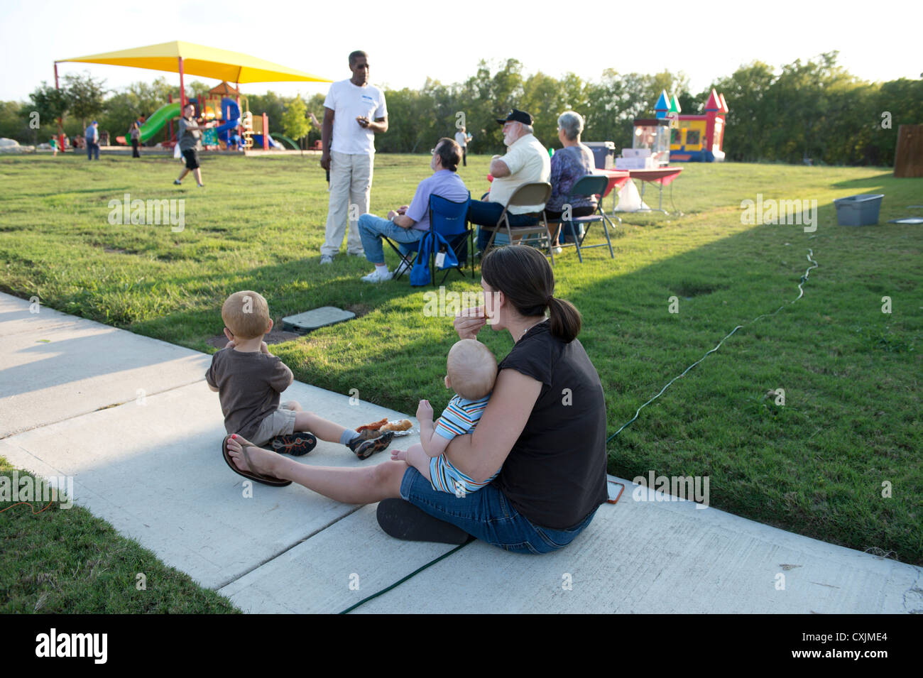 Families gather at neighborhood park with police for the annual  National Night Out gathering to interact with neighbors - Stock Image