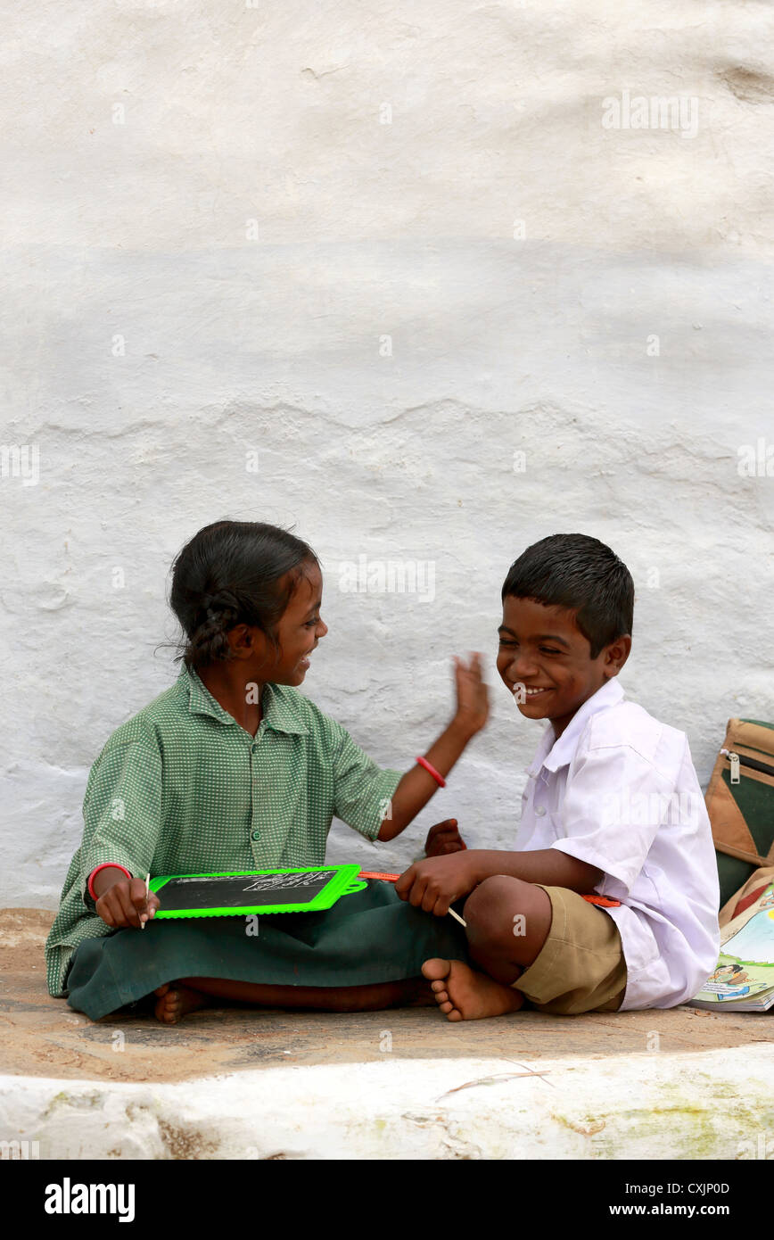Indian school children best friends but giving him a gentle slap Andhra Pradesh South India - Stock Image