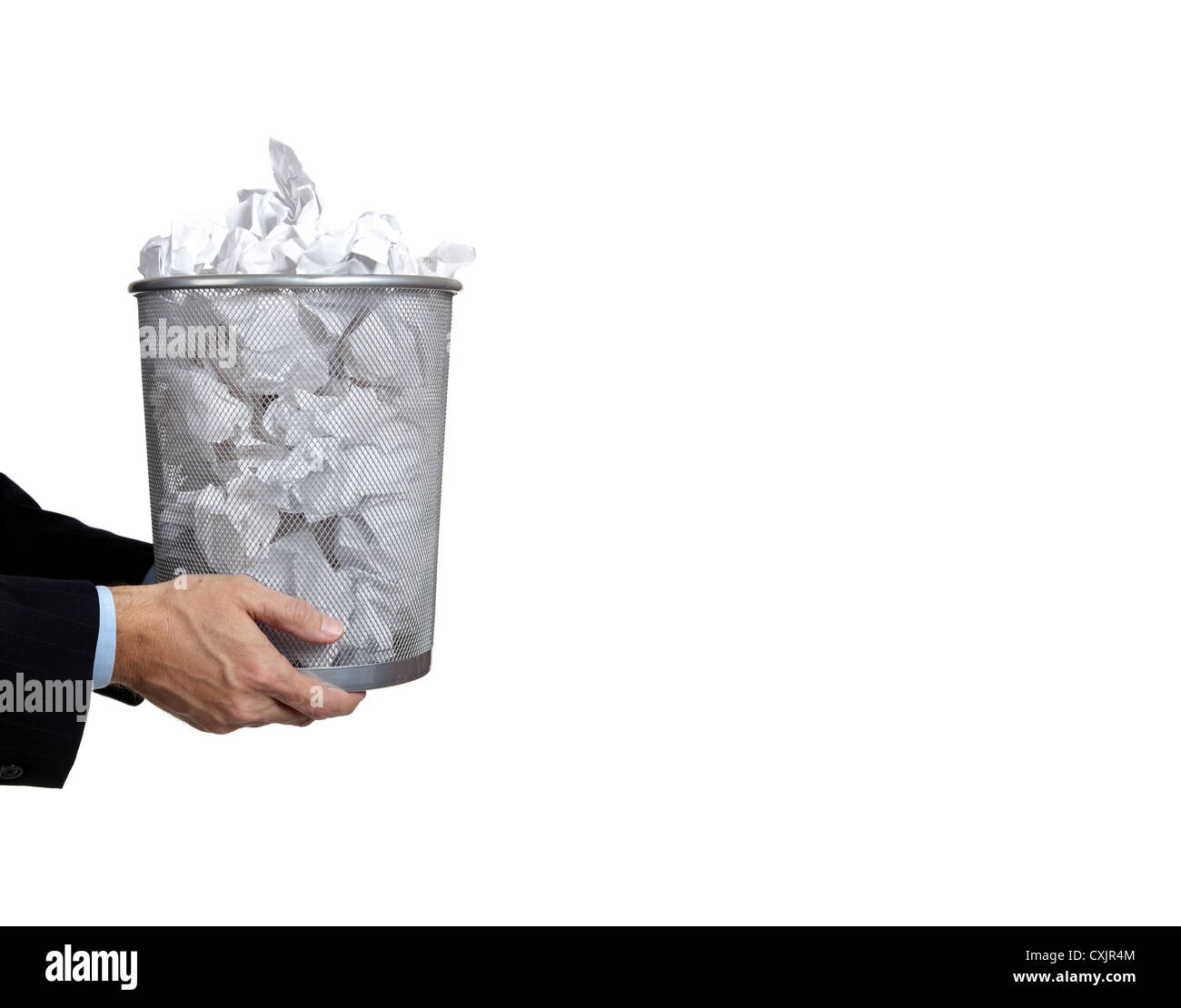 Business man's hands holding a wire mesh trash can with crumpled paper in it on a white background with copy - Stock Image