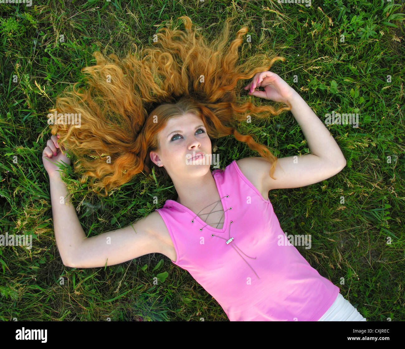 young redheaded woman lying on the grass in summer day - Stock Image