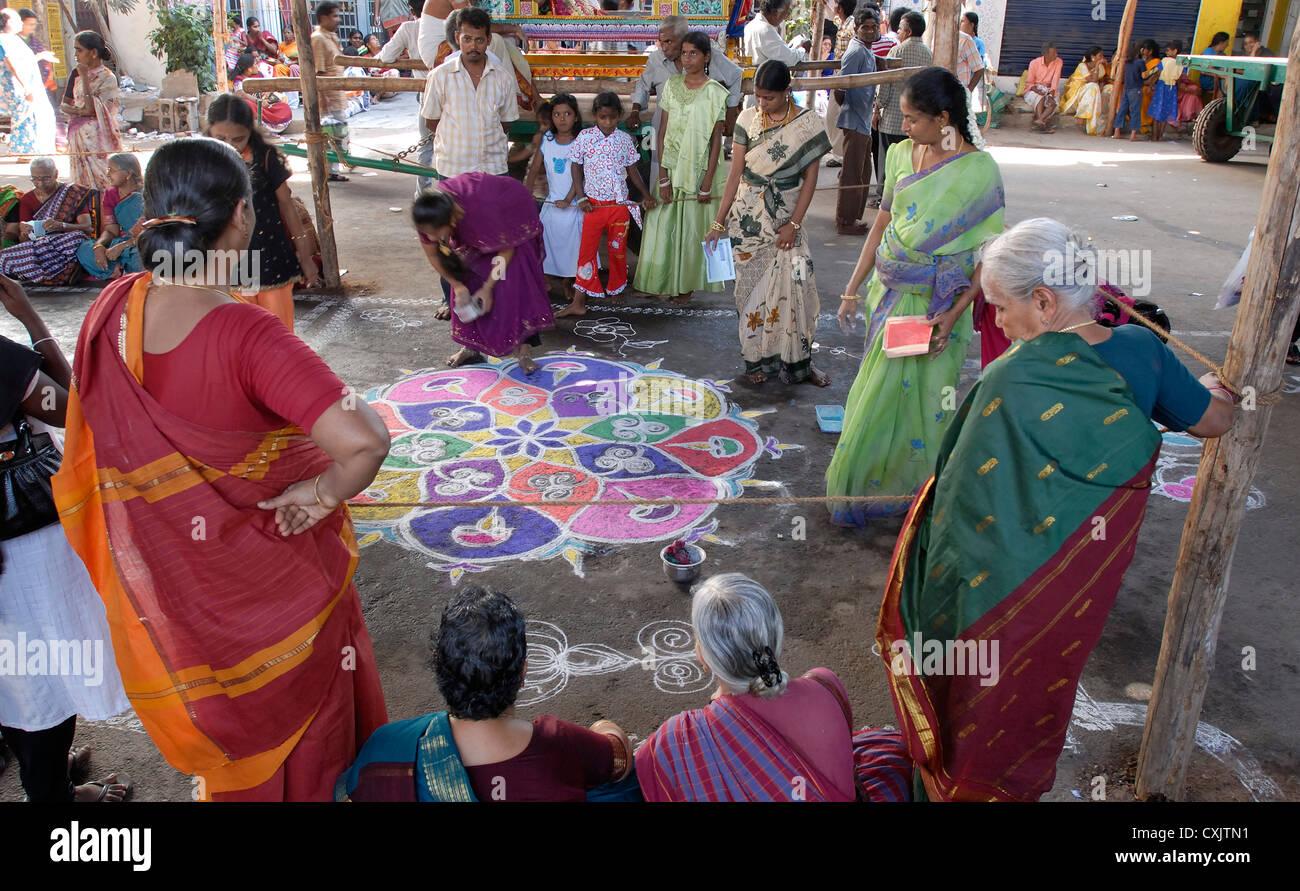 Making Kolam;Rangoli in front of kapaleeswarar temple during Arupathumoovar festival in Mayilapore, Chennai ,Tamil Stock Photo
