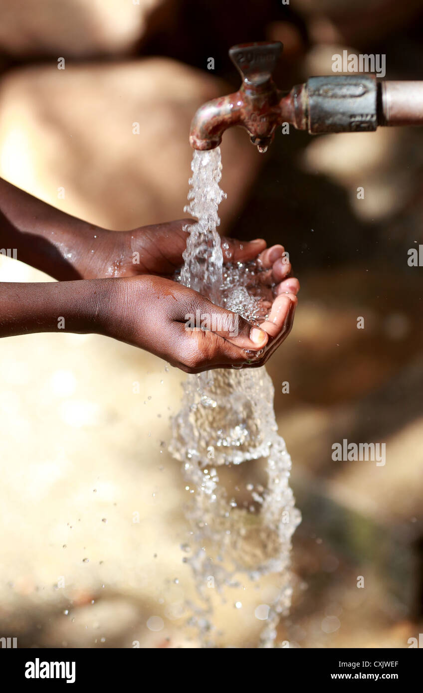 Young Indian girl holding running water Andhra Pradesh South India - Stock Image