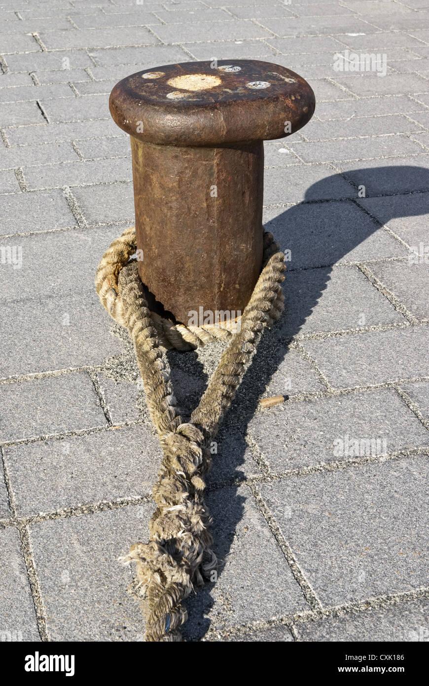 Bollard with rope Stock Photo