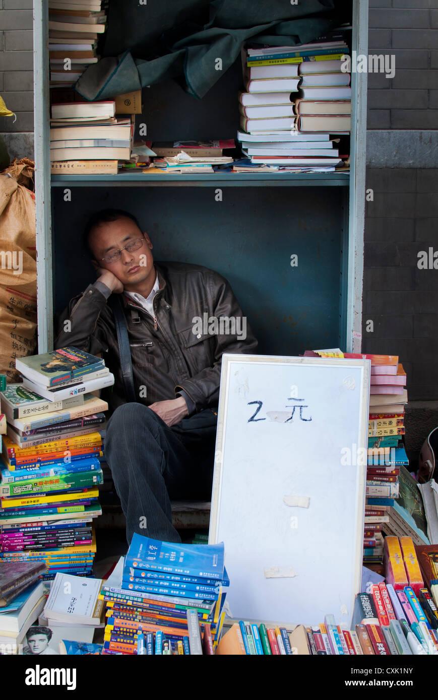 Second-hand book  seller sleeping at Panjiayuan market, Beijing - Stock Image