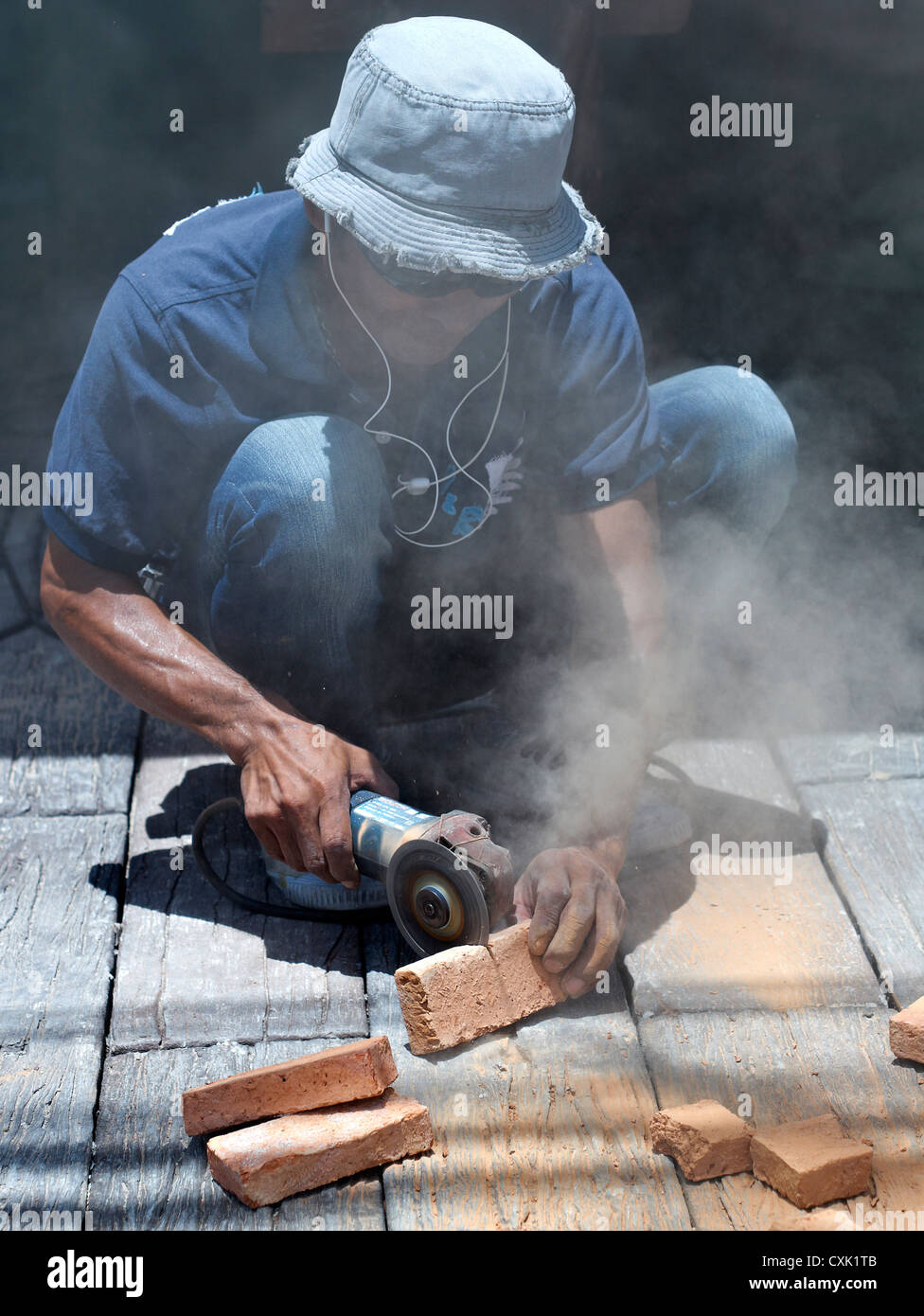 Builder using a hand powered angle grinder to cut bricks. Thailand S.E. Asia Stock Photo