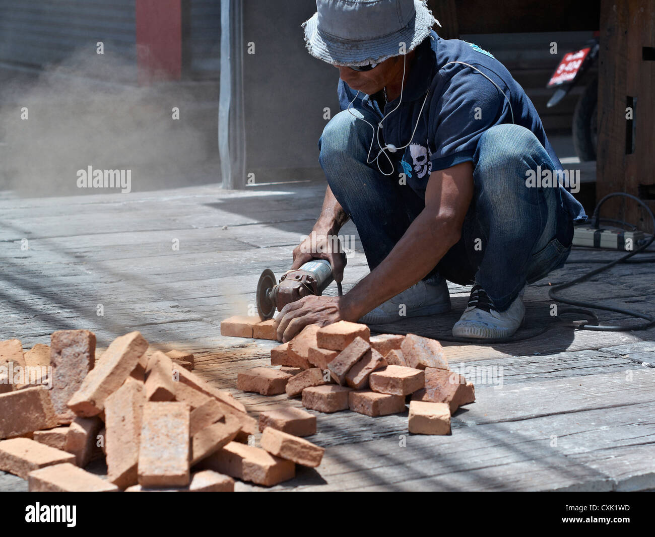Builder using a hand powered angle grinder to cut bricks. Thailand S.E. Asia - Stock Image