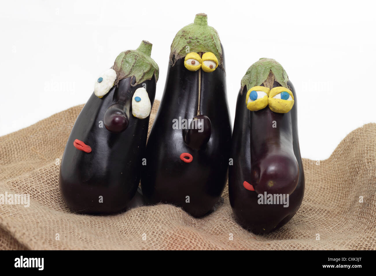 three nosed eggplants with plasticine eyes - Stock Image