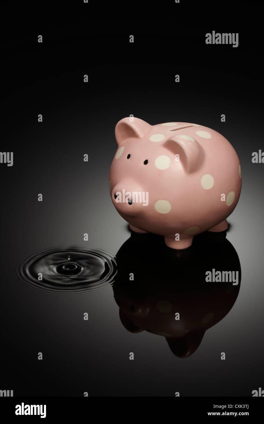 Piggy Bank with Droplet of Water in Puddle - Stock Image