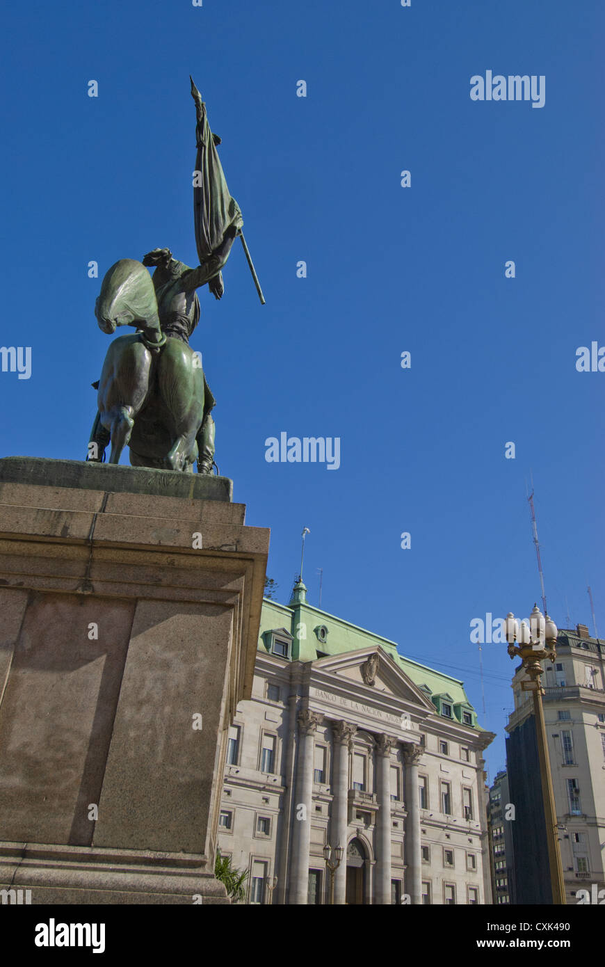 Statue of General Manuel Belgrano with flag in Plaza de Mayor by Bank of the Argentine Nation, Buenos Aires, Argentina - Stock Image
