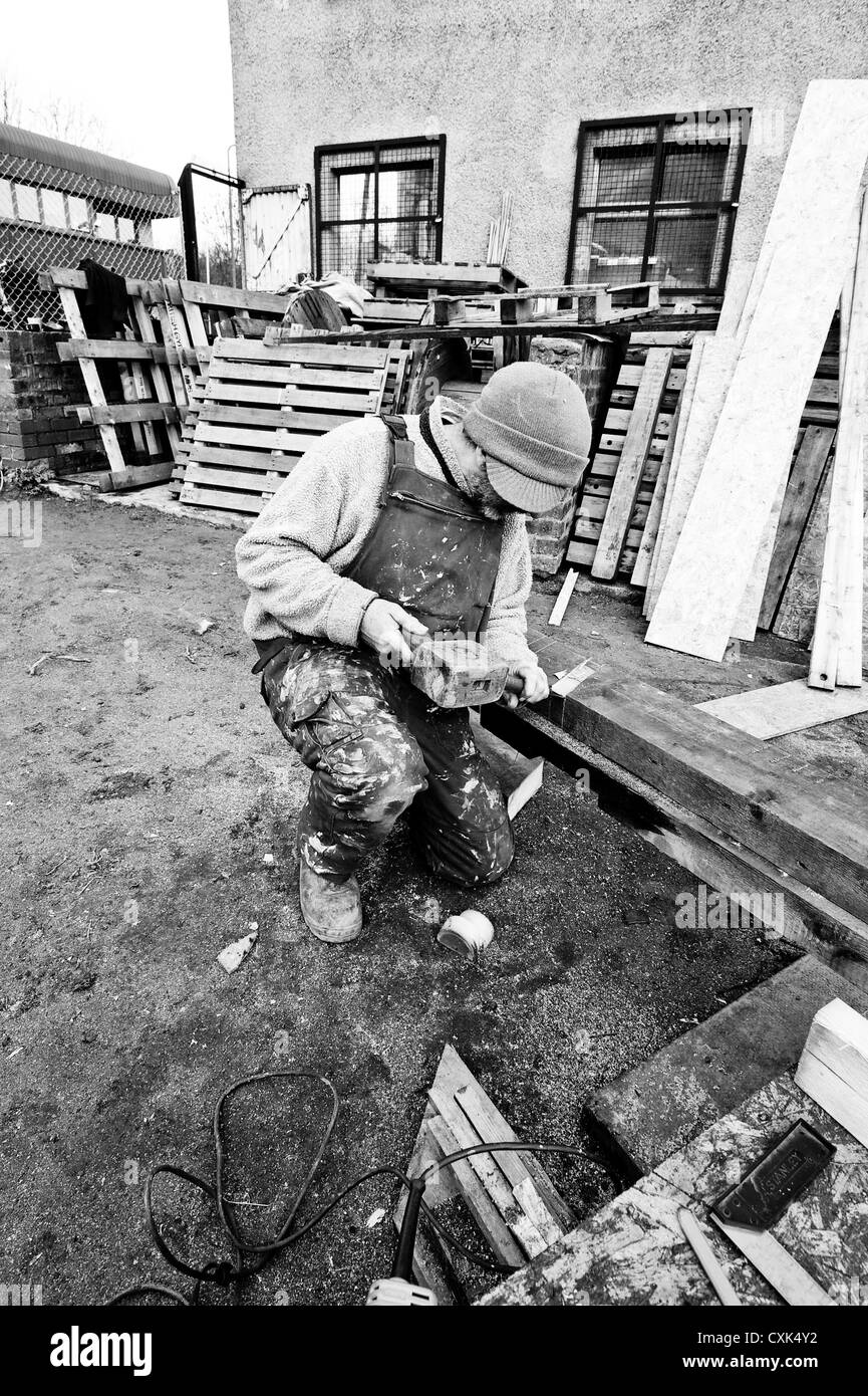 Man on a muddy construction site using an old fashioned wooden mallet and chisel. - Stock Image