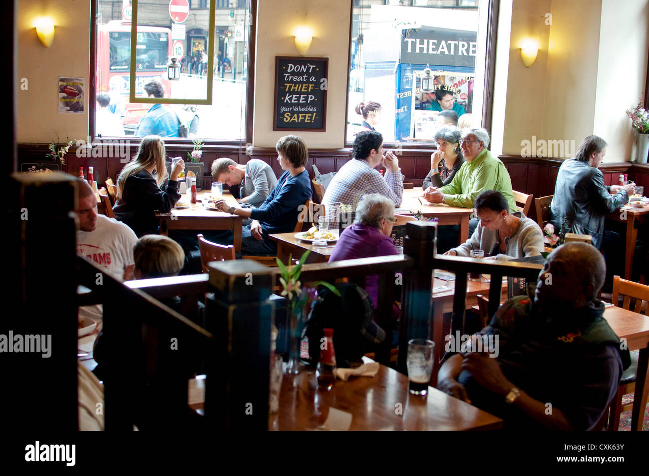 London pub diners with warning sign about thieves on the wall. Unidentified people. Public place. Editorial use. - Stock Image