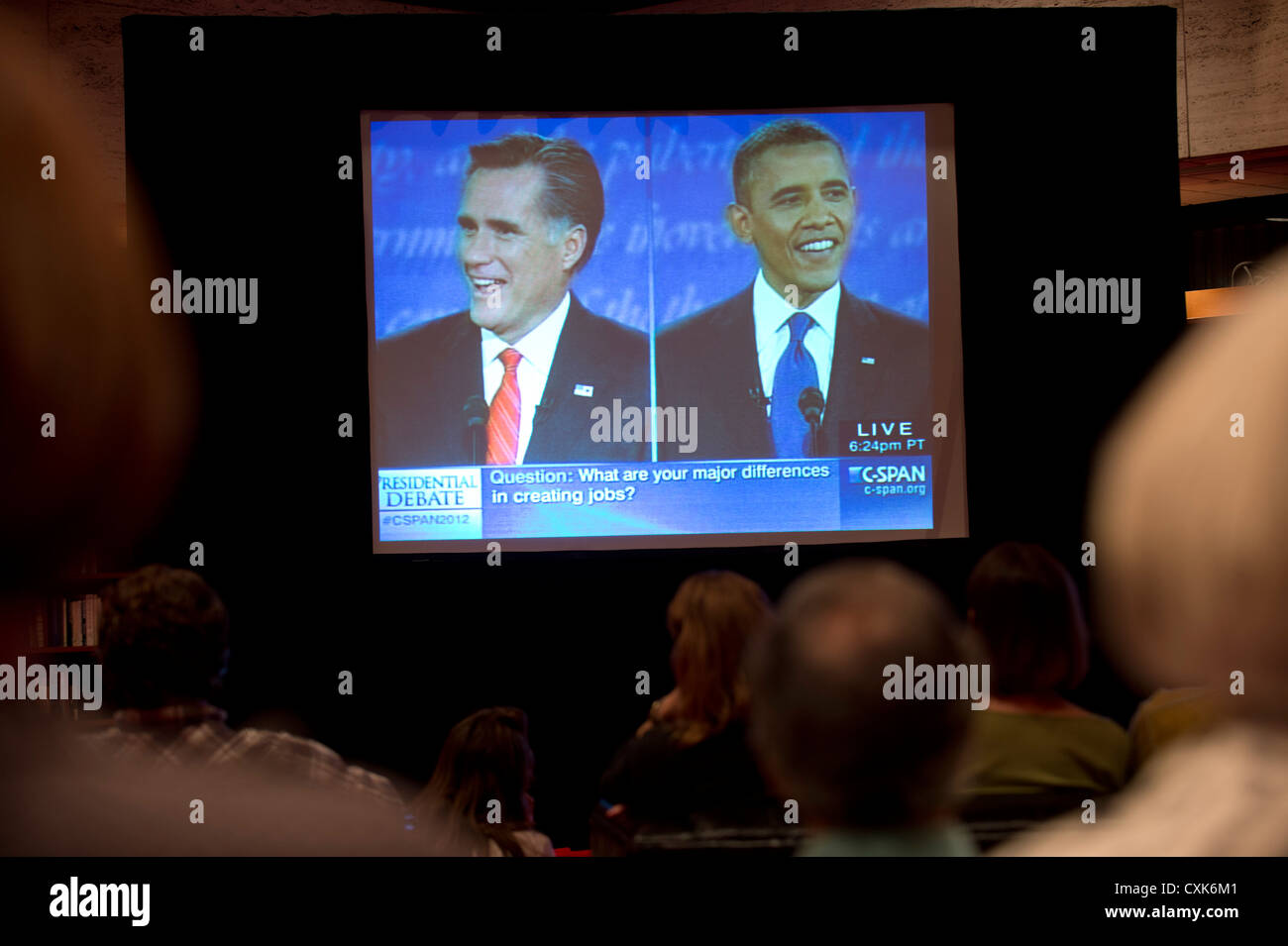 Likely voters watch large TV screen showing televised debate between US presidential candidates Barack Obama and - Stock Image