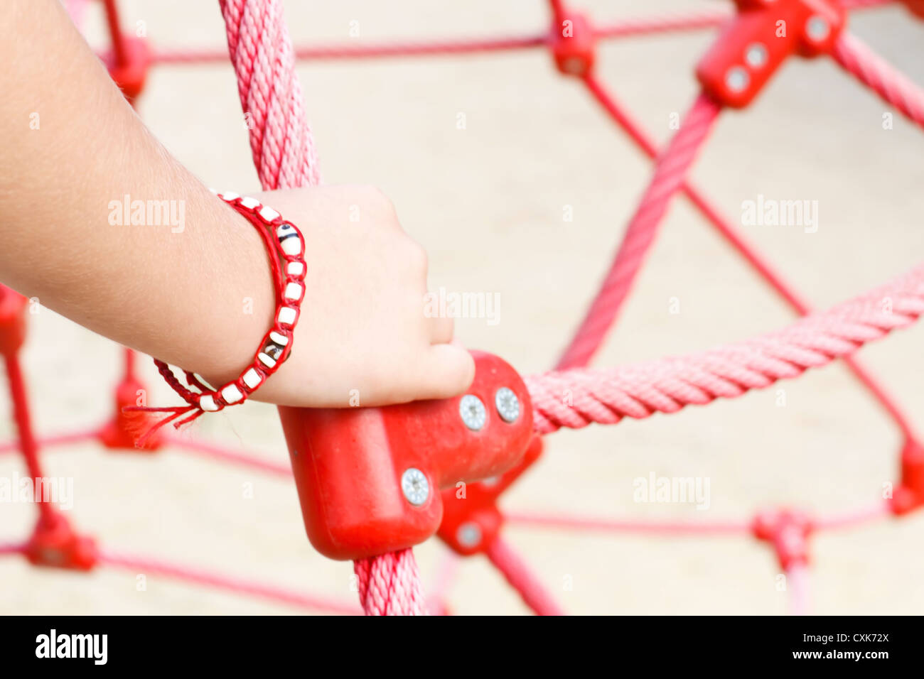 Boy's (6-7) hand holding red rope, France. - Stock Image