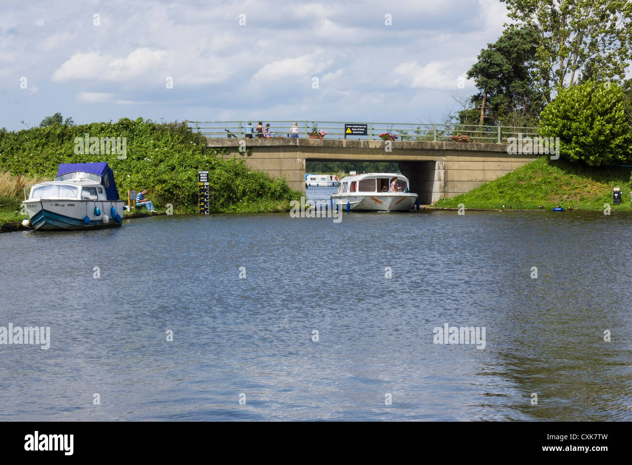 cruising boat with a family on board, passing under Ludham bridge, Norfolk broads, Norfolk - Stock Image
