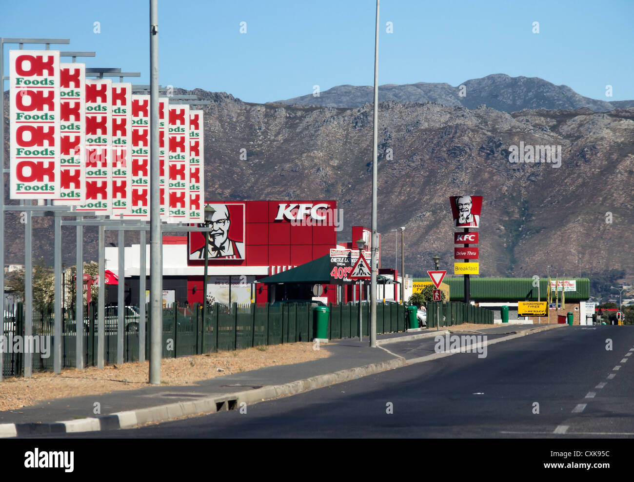 OK Store and KFC ads against a mountainous backdrop near Gordon's Bay, Western Cape,South Africa - Stock Image