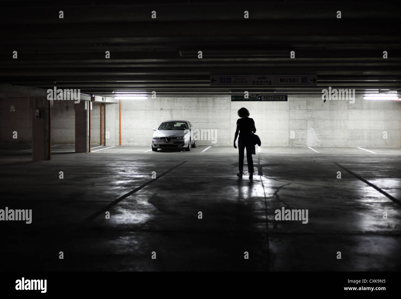 A lone woman returns to her car in a lonely underground car park. - Stock Image
