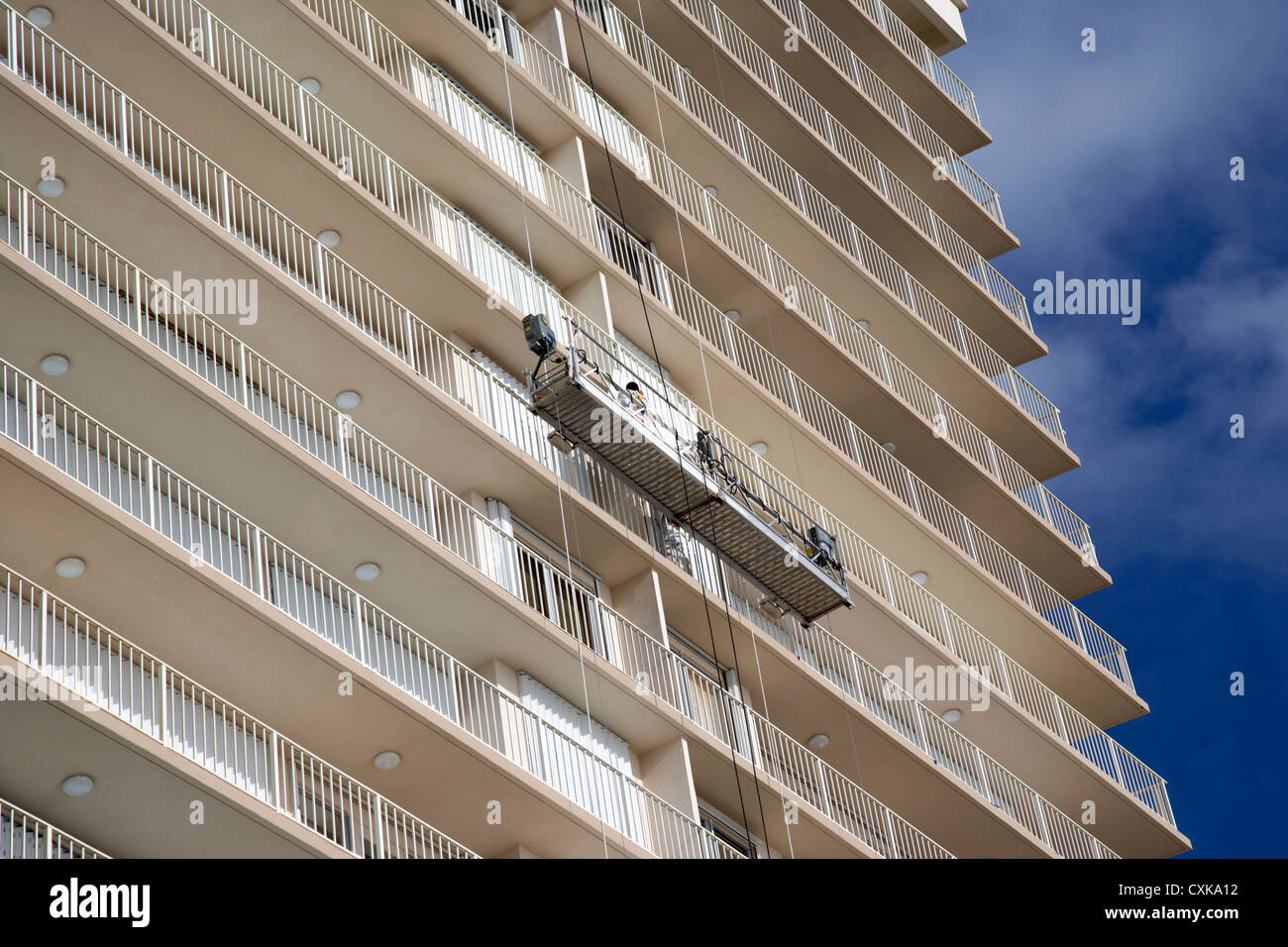 maintenance and cleaning crew on platform lift on apartments beachfront developments fort lauderdale beach florida - Stock Image