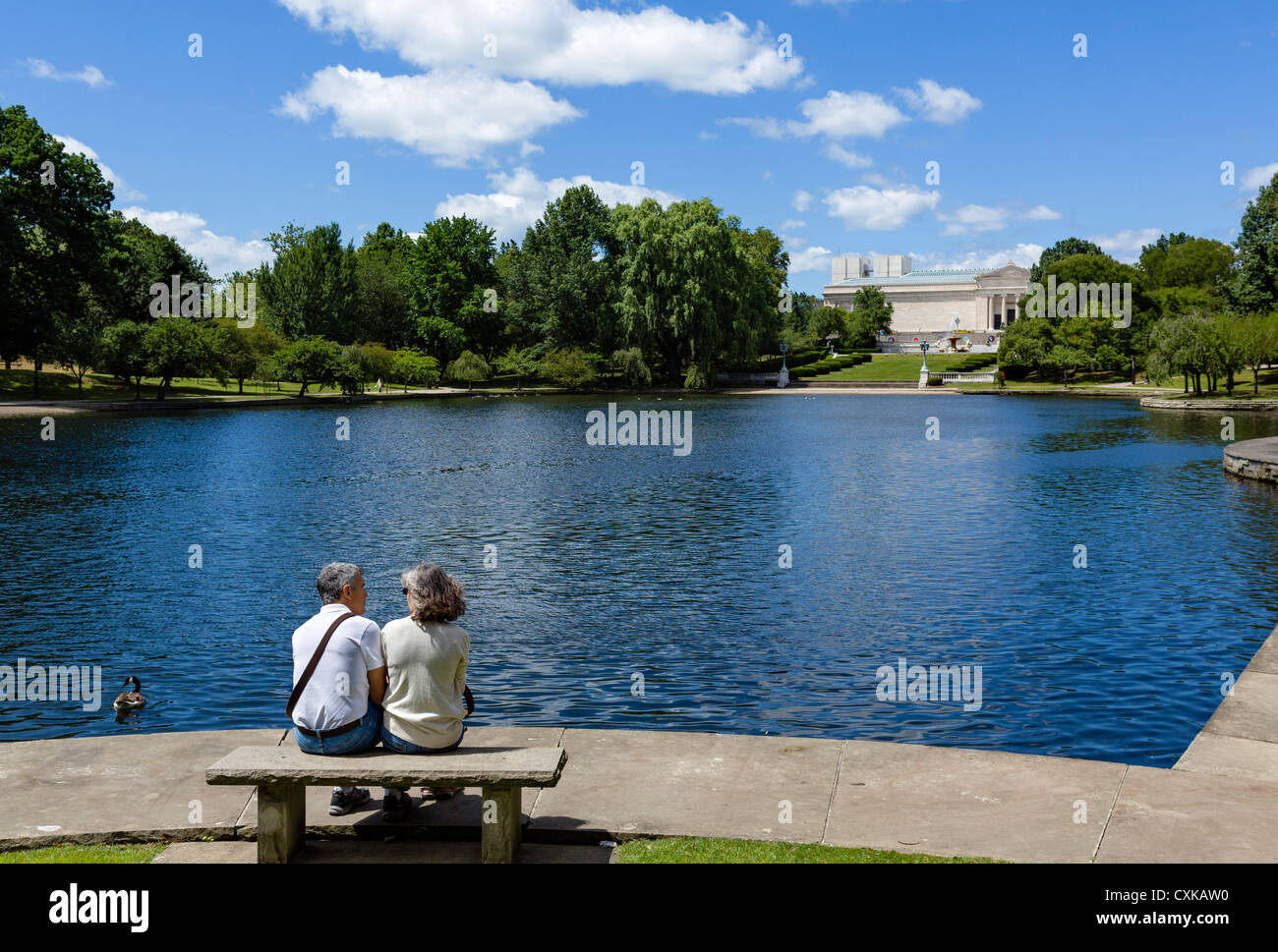 Couple sitting on a bench by Wade Lagoon Cleveland Museum of Art behind, University Circle district, Ohio, USA - Stock Image