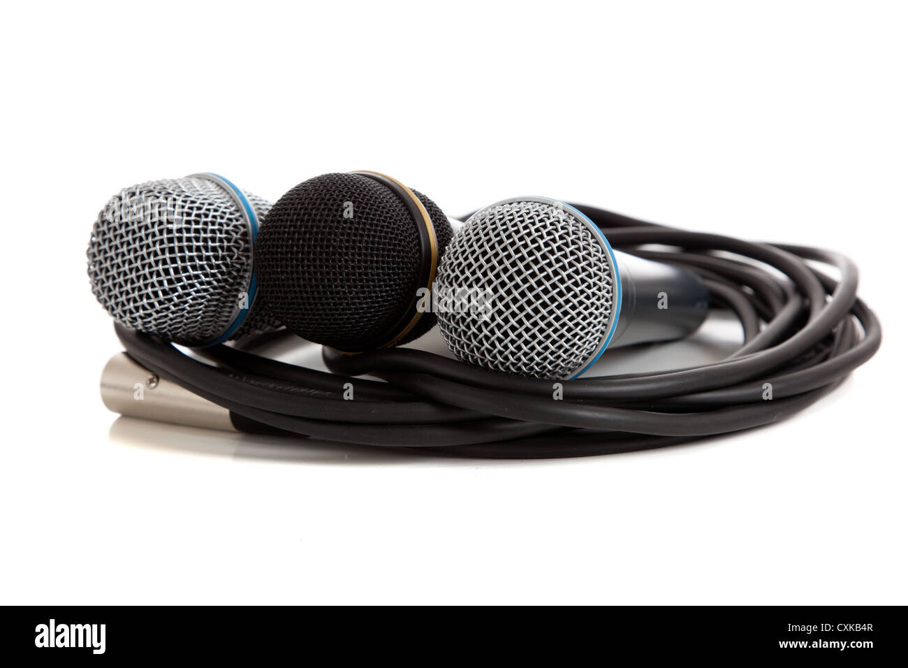 Trio of microphones with cords on a white background - Stock Image