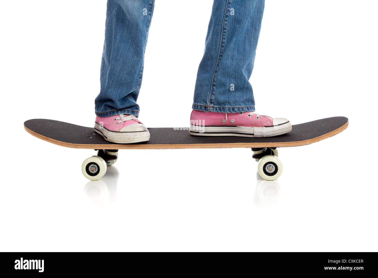Pink sneakers on a skate board - Stock Image