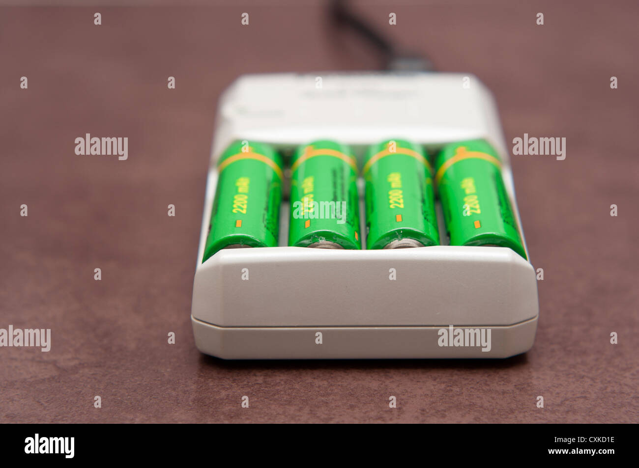 AA rechargeable batteries charging in mains electricity charger. - Stock Image