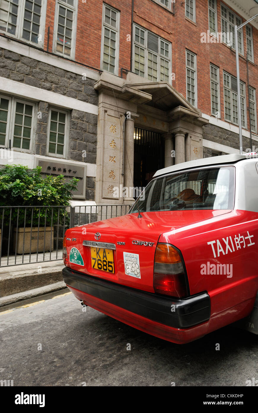 Red Hong Kong taxi travelling uphill. - Stock Image