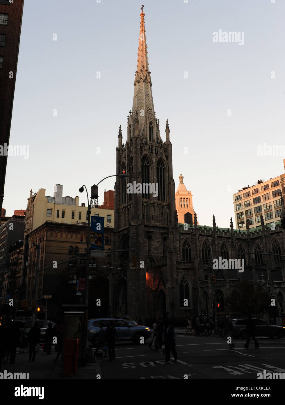 Rush-hour twilight view, to Edison Consolidated Building, Grace Church, cars, people, Broadway at East 10th Street, - Stock Image
