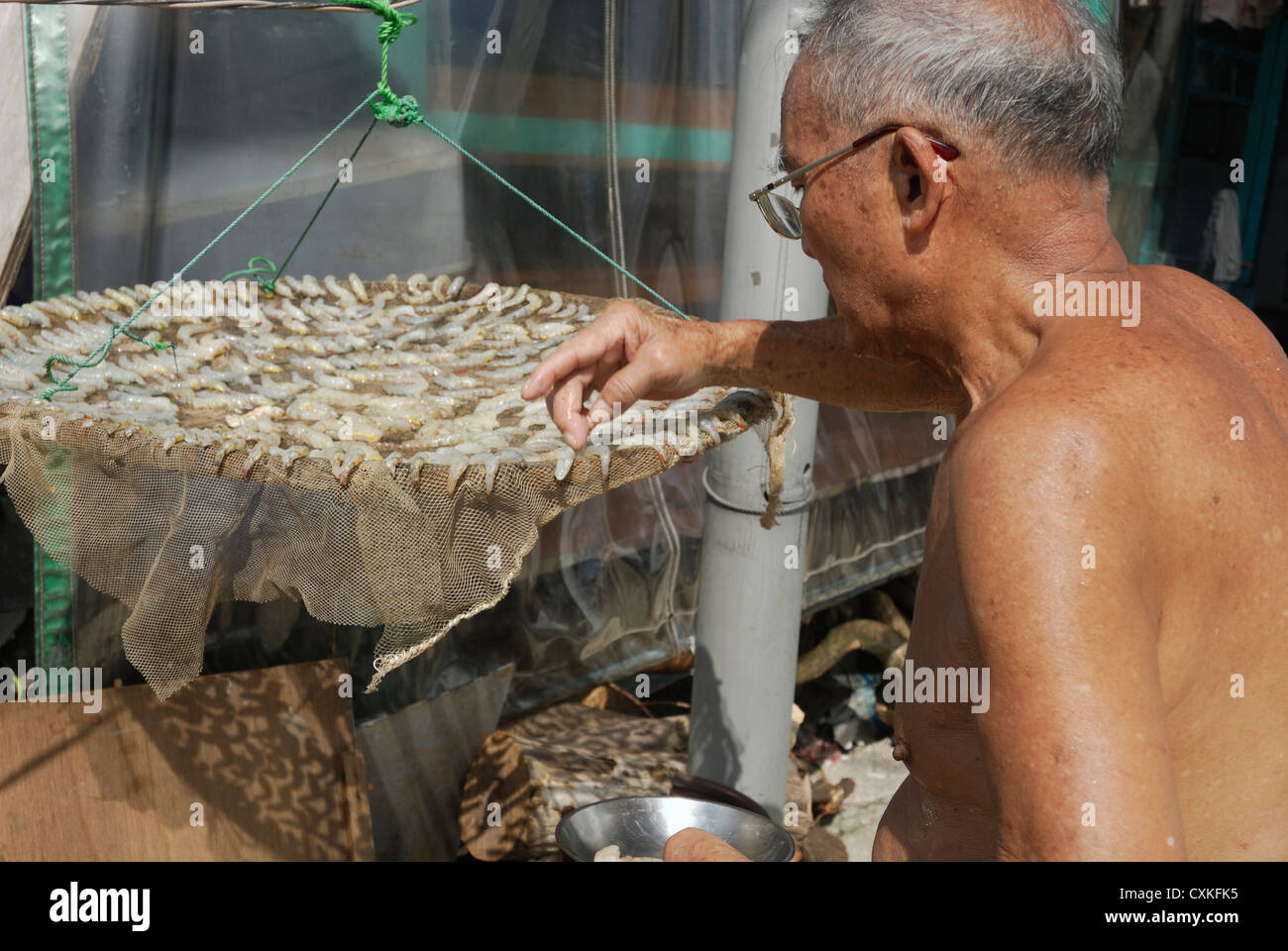 Tai O village man drying shrimp in the hot sun. - Stock Image