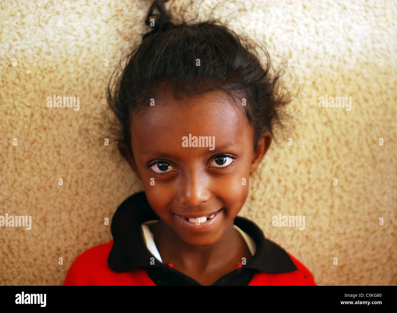 Eritrea, Asmara, close-up portrait of an African school girl smiling against wall. (MR) Stock Photo