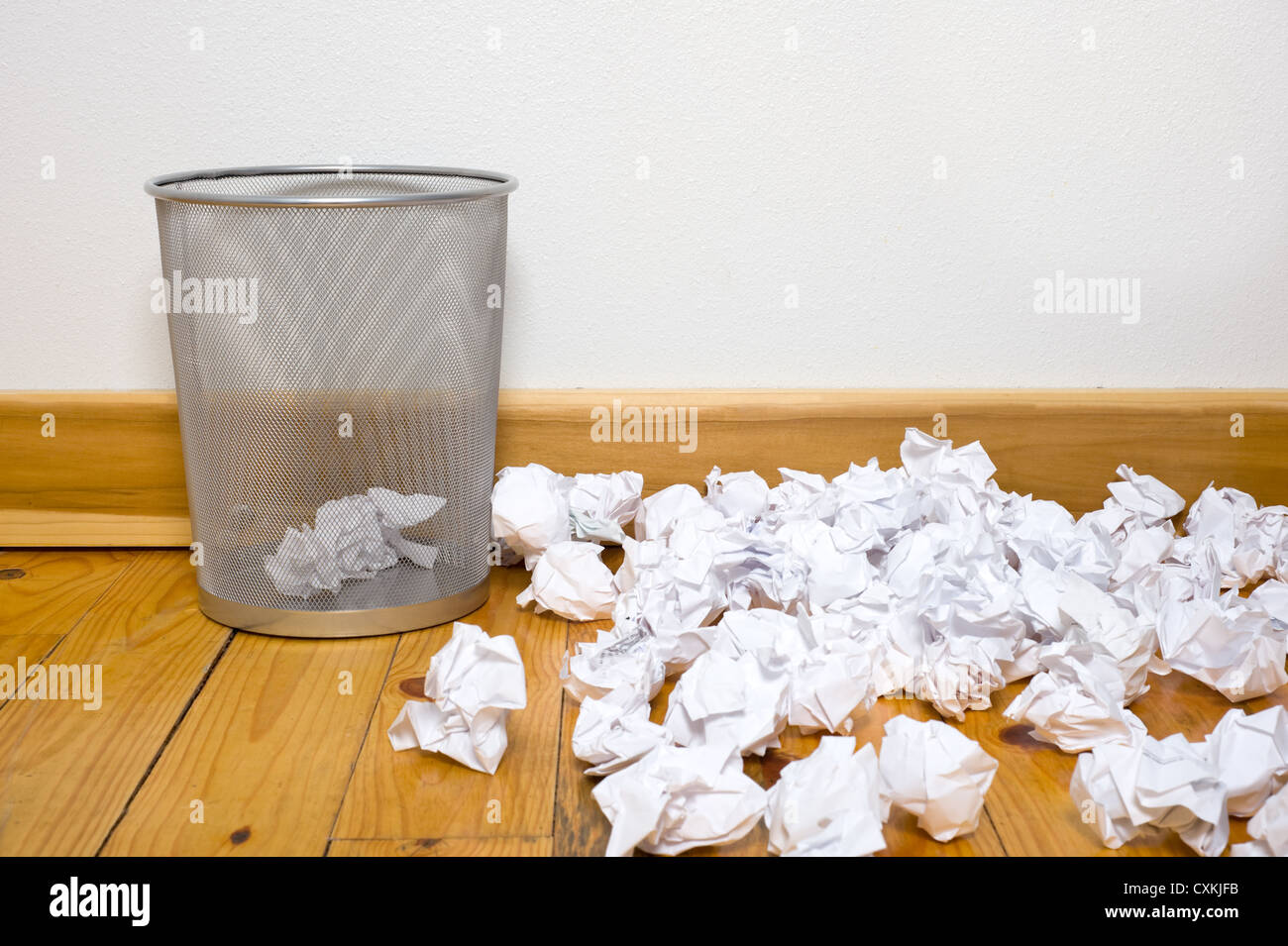 a wire mesh office trash can with crumpled paper on a wooden floor with a white wall, includes copy space - Stock Image