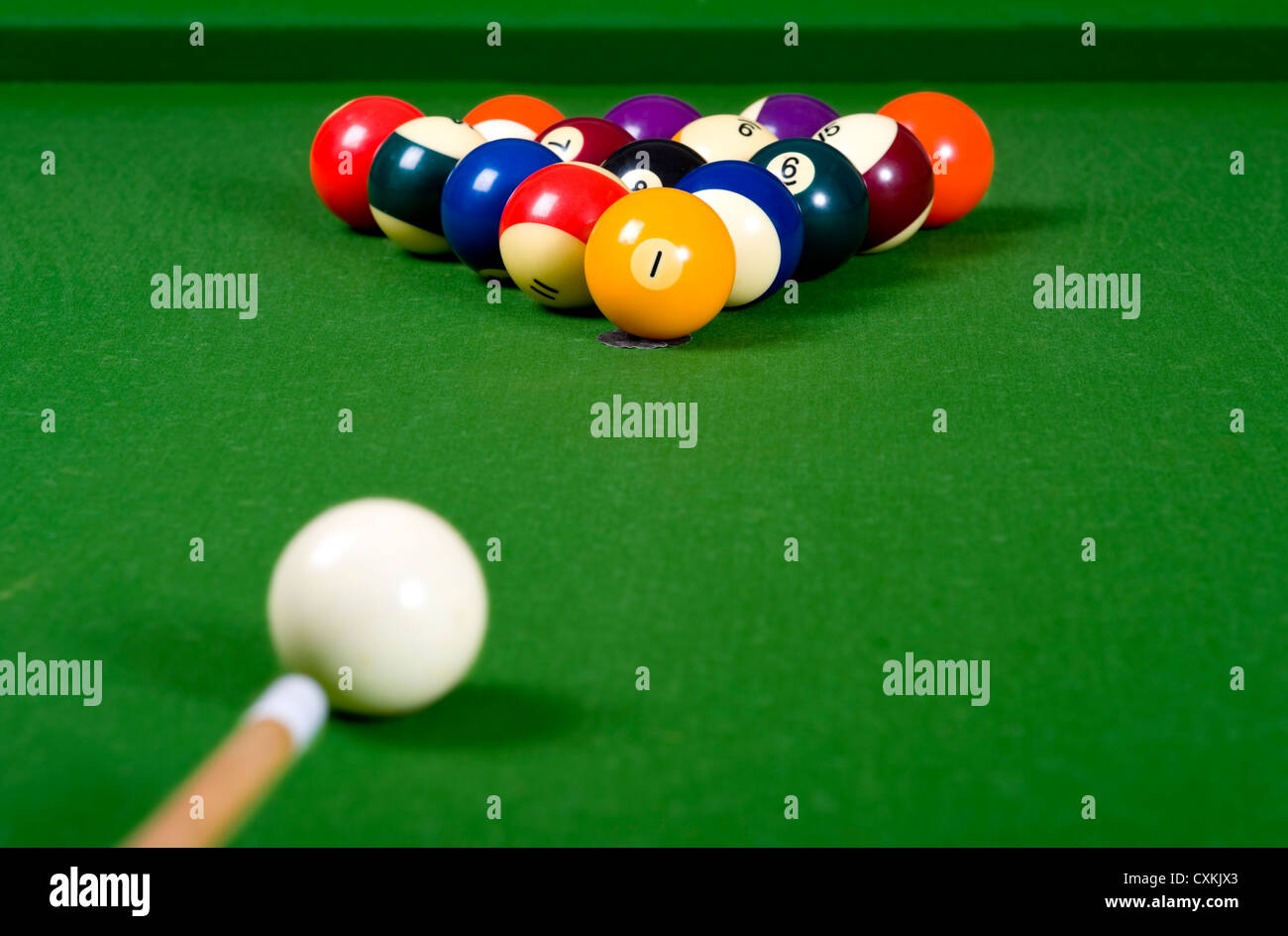 A game of pool with the balls lined up in an 8-ball formation on a green felt pool table - Stock Image