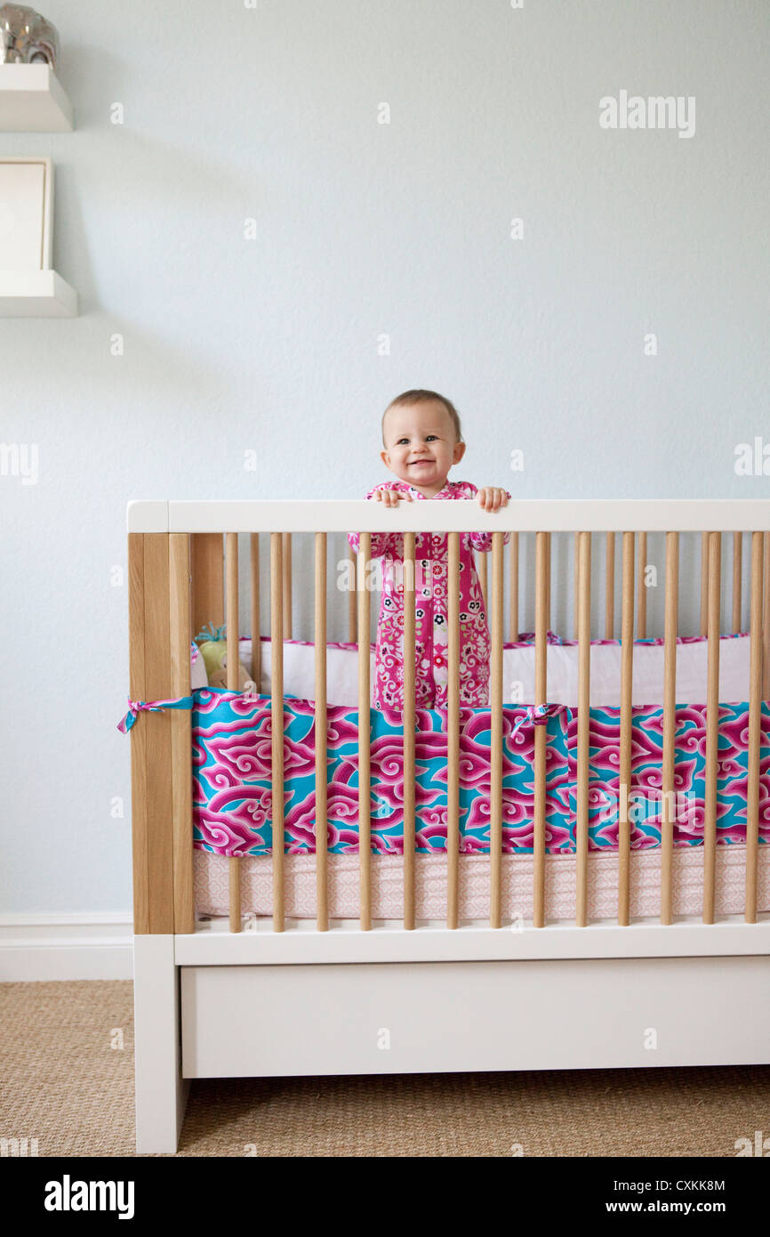 Baby girl standing in crib - Stock Image