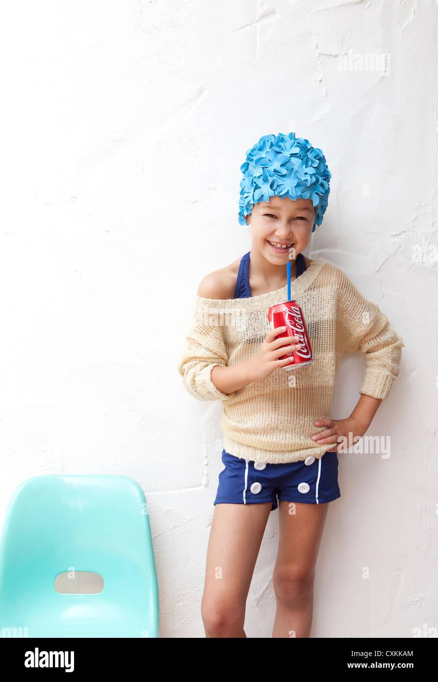 Girl in bathing suit drinking soda - Stock Image