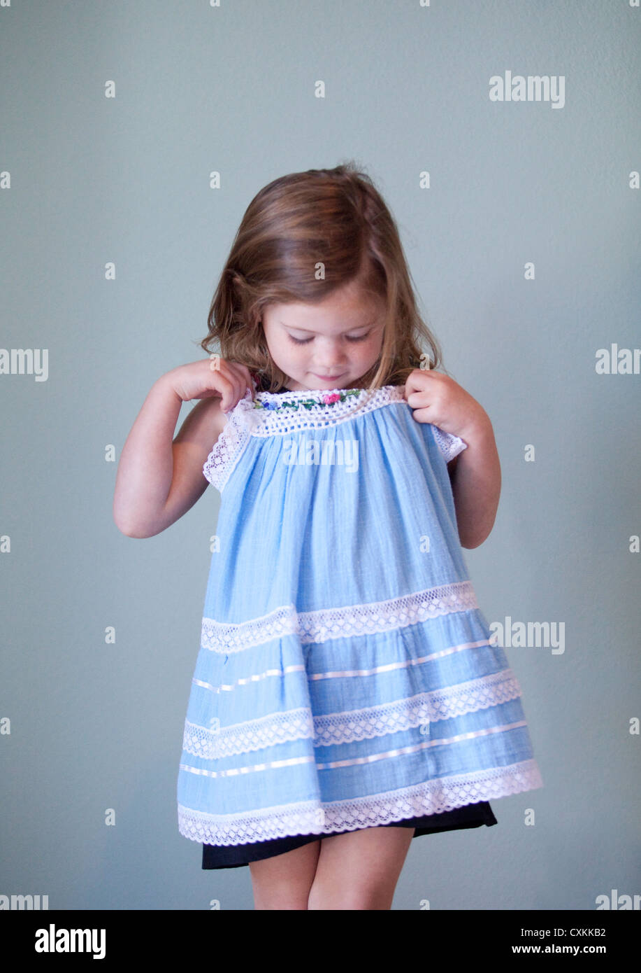 Young girl holding blue dress - Stock Image