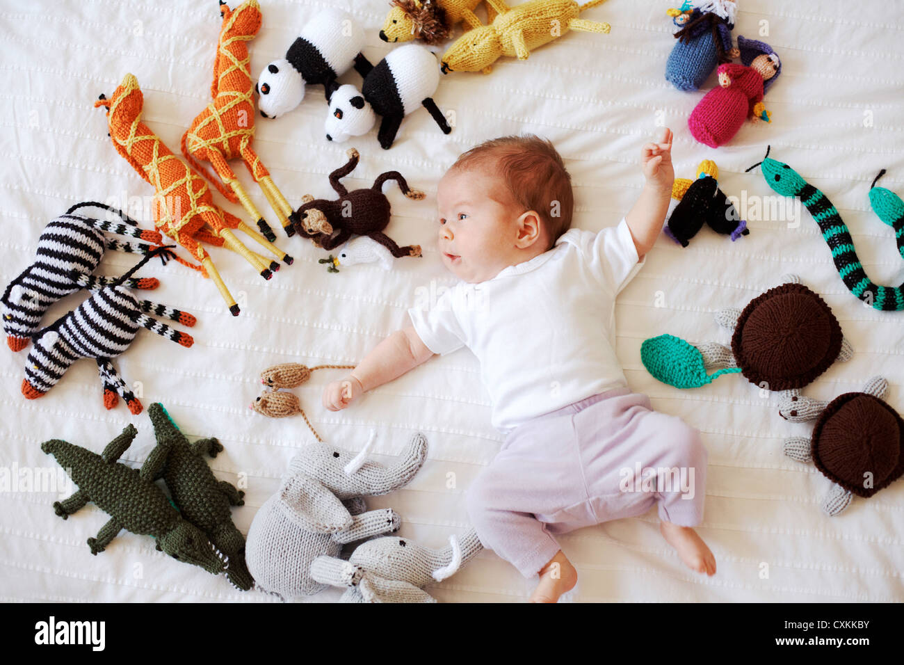 Baby surrounded by stuffed toys - Stock Image