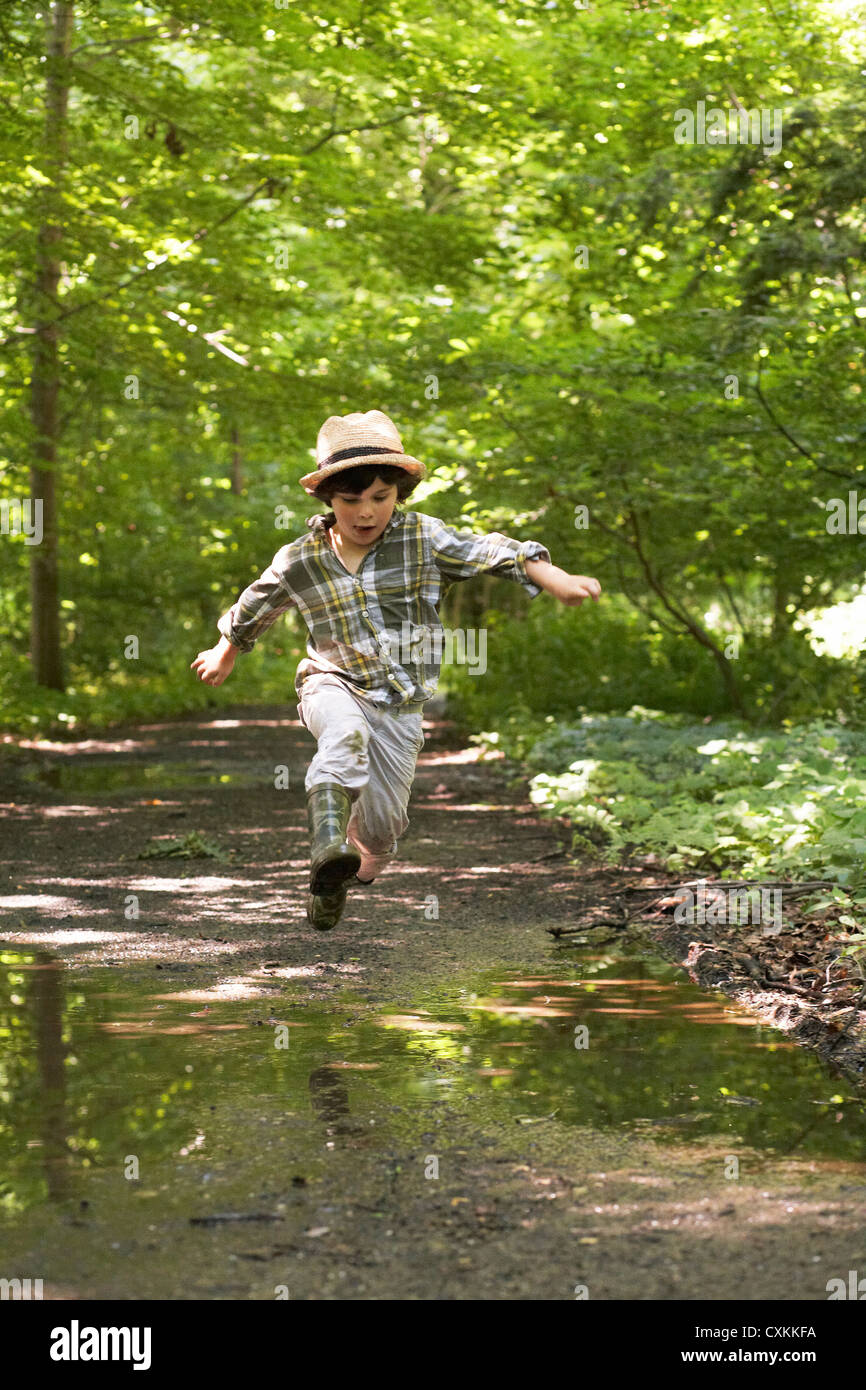 Young boy jumping over puddles - Stock Image