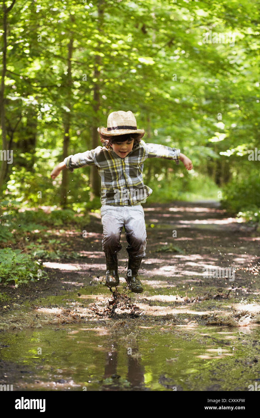 Young boy jumping in puddles - Stock Image