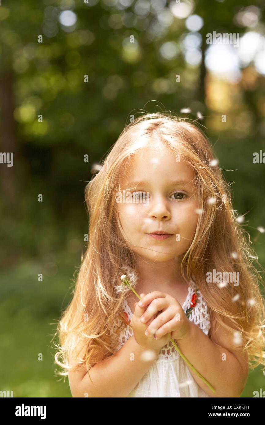 Little girl wishing on a dandelion - Stock Image