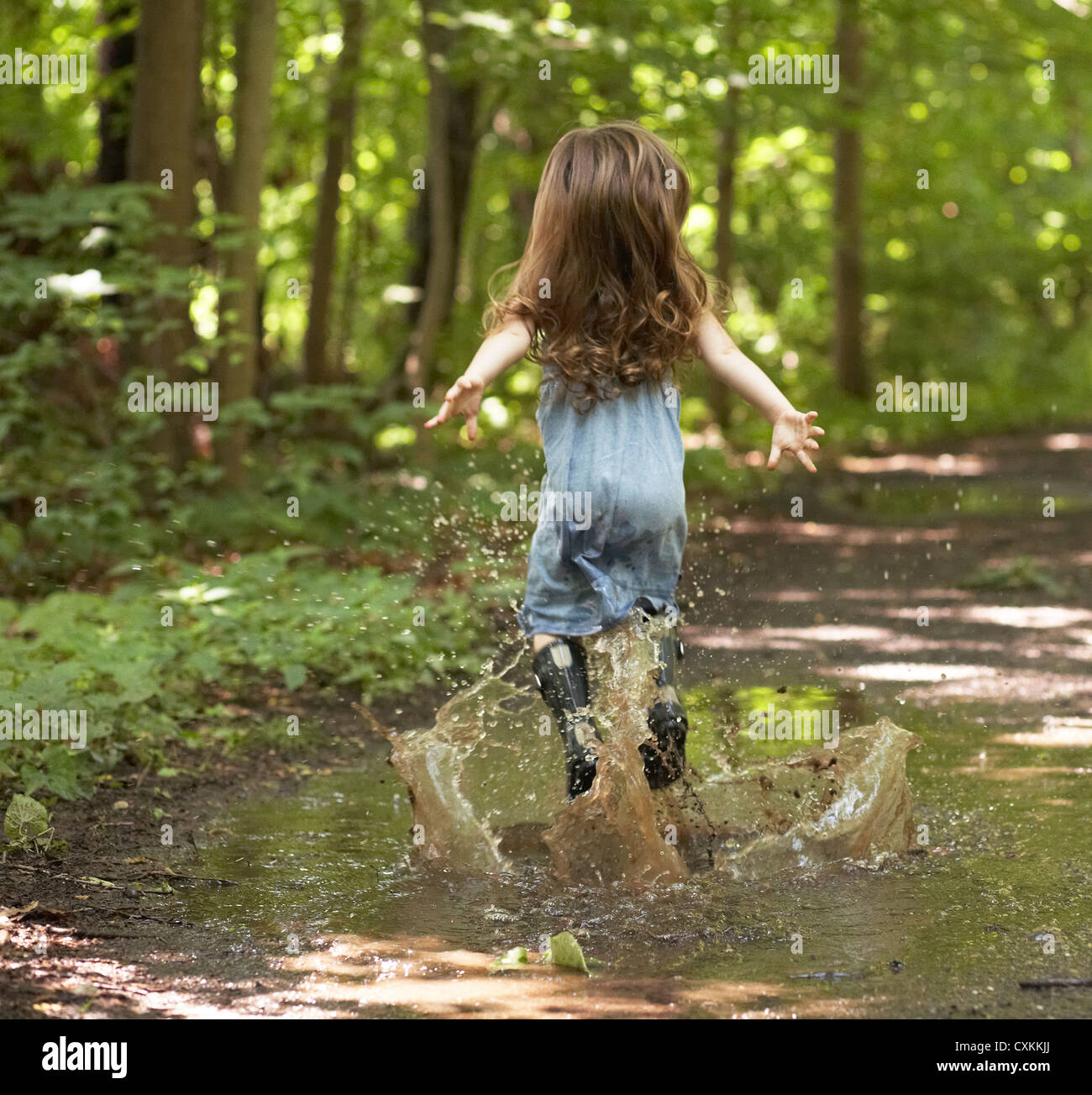 Little girl jumping in puddle - Stock Image