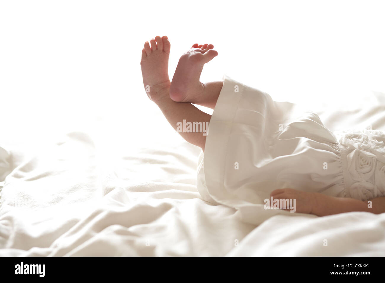 Baby girl in dress laying on bed - Stock Image