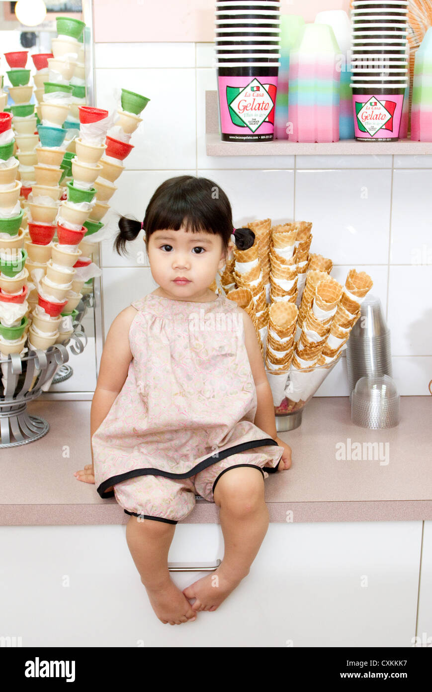 Little girl on counter in ice cream shop - Stock Image