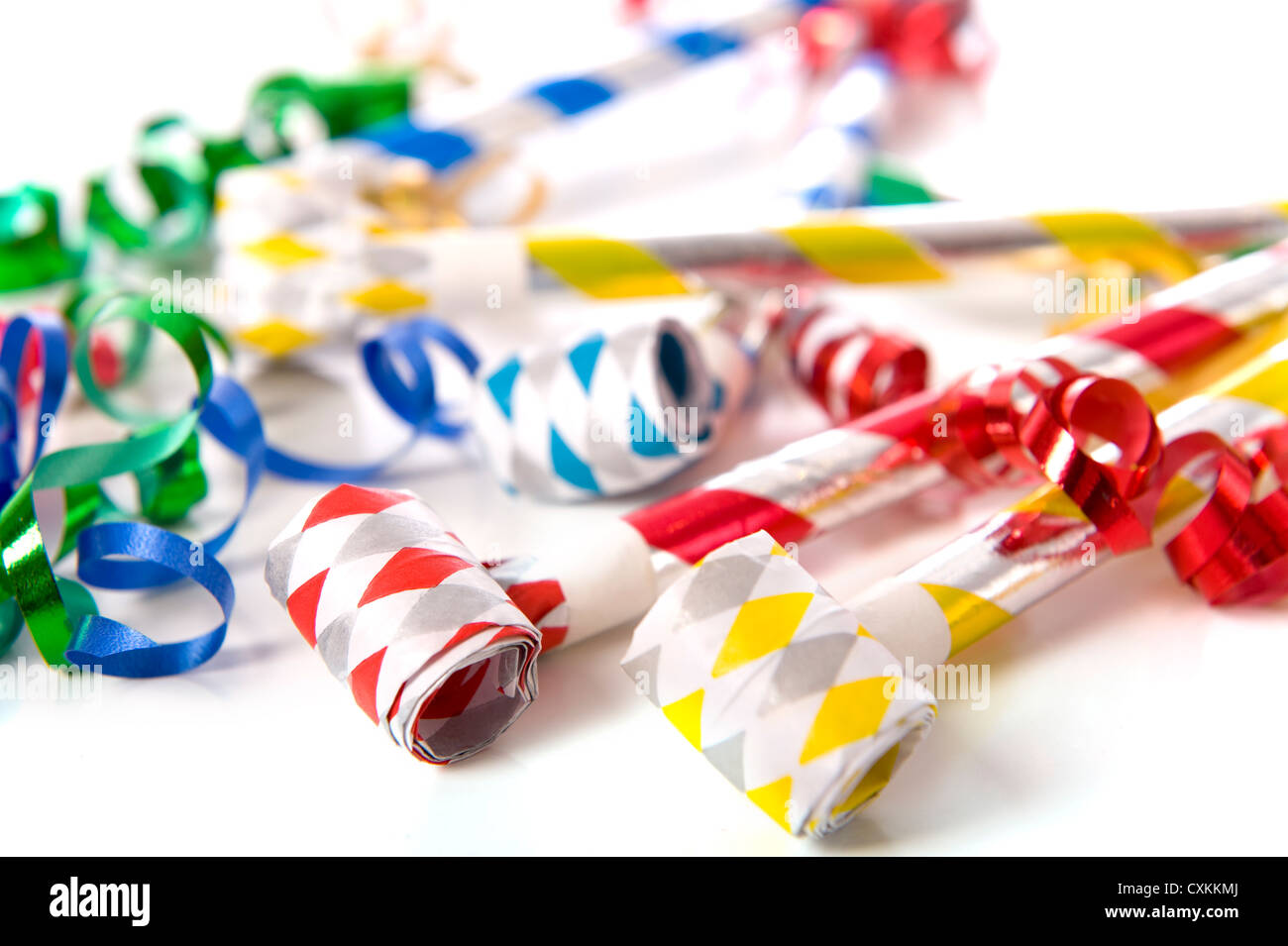 A group of party items, noisemakers and ribbons, on a white background, New Years theme - Stock Image