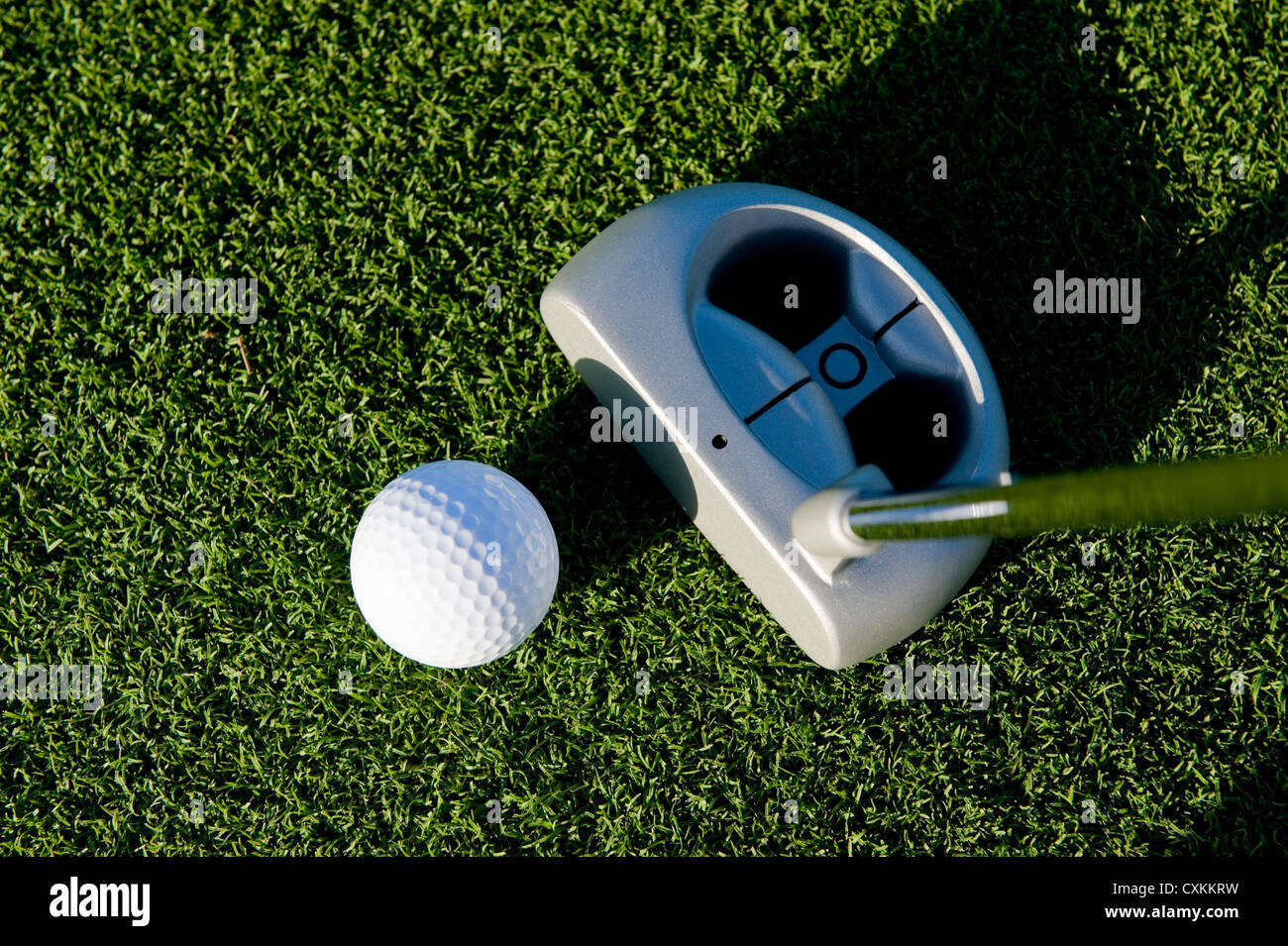 A short putt in the game of golf with a ball and a putter - Stock Image