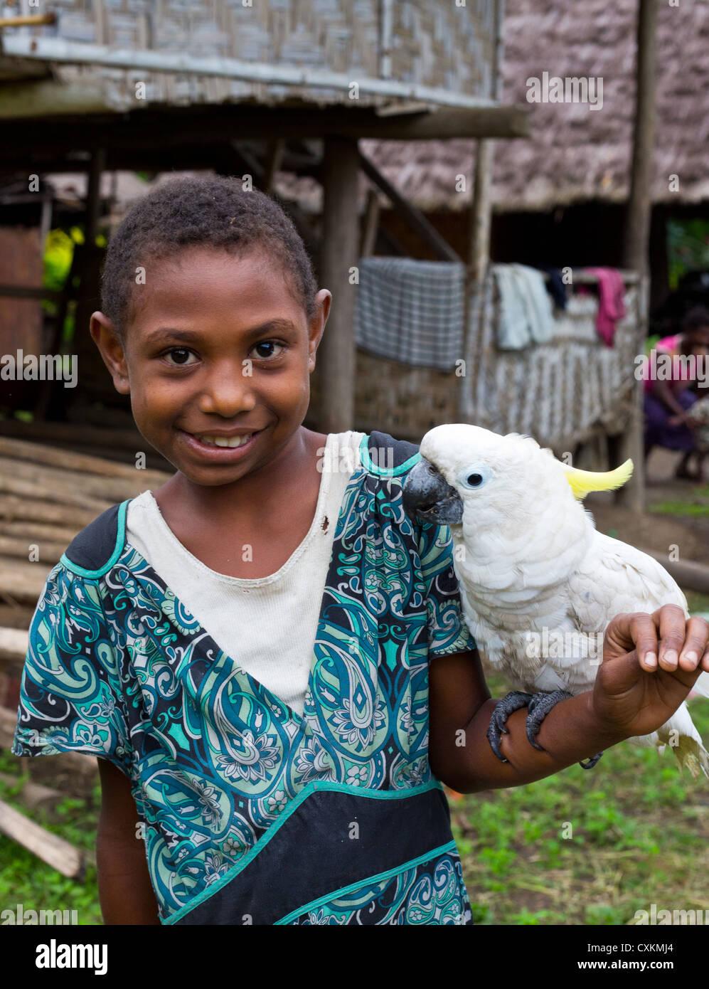 Young village girl smiling and holding a Triton Cockatoo (Cacatua galerita triton) , Erap valley, Papua New Guinea - Stock Image