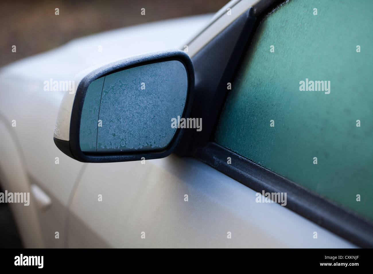 Icy car in winter, ice on the rearview mirror and on the windows - Stock Image