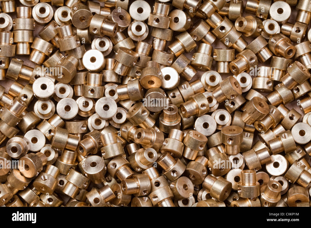 A pile of small, industrially produced parts made of brass - Stock Image
